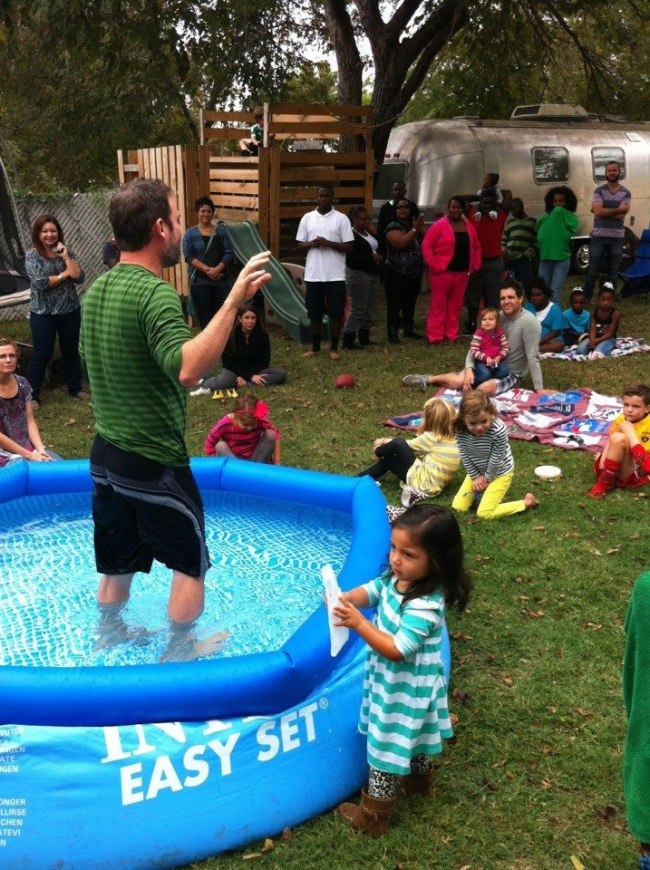 A small church gathers for a baptism in a backyard pool